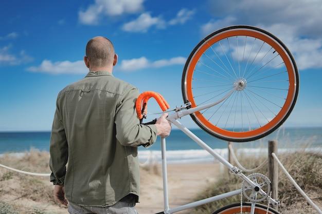 ビーチで彼のオレンジ色の自転車を持ち上げている男性のクローズアップショット