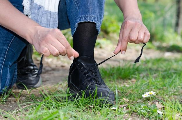 잔디 덮인 필드에 그의 신발 끈을 묶는 남성 손의 근접 촬영 샷