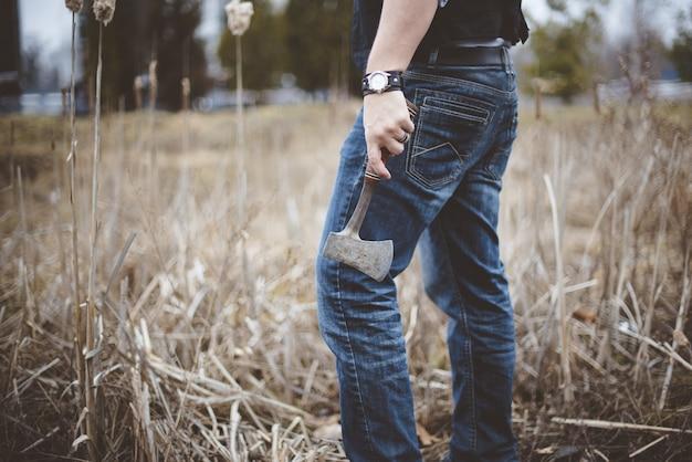 立っていると小さな斧を保持している男性のクローズアップショット