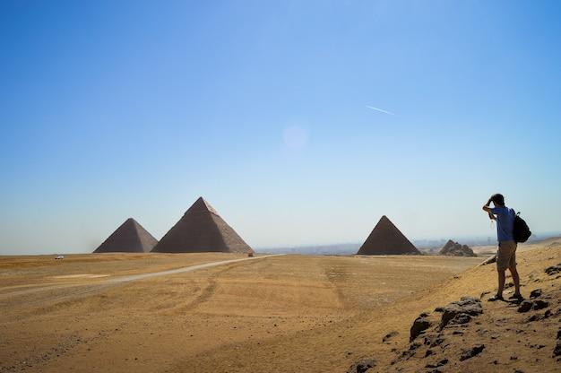 이집트의 기자 묘지를보고 서있는 남성의 근접 촬영 샷