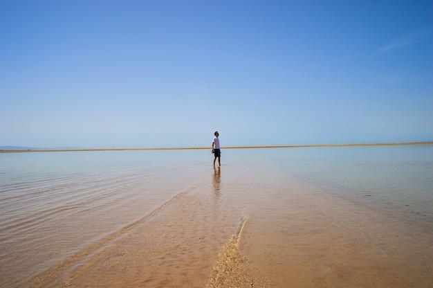 晴れた日にビーチを歩いている男性のクローズアップショット
