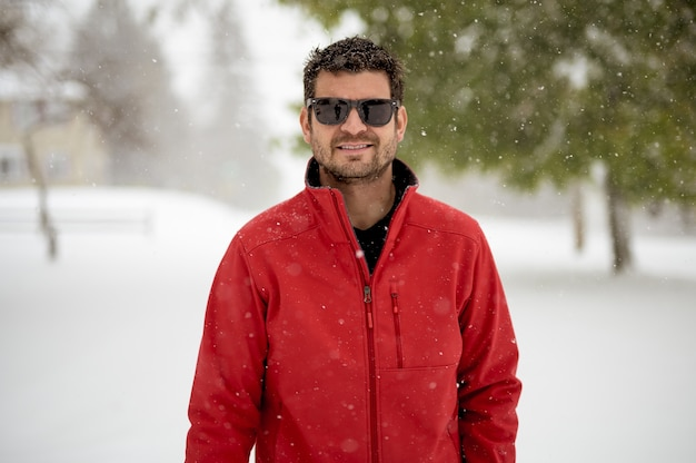 赤いジャケットを着て、カメラを見ながら笑っている男性のクローズアップショット
