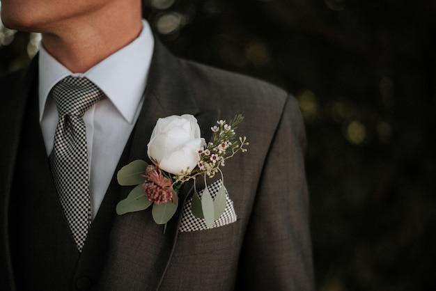 ポケットにブートニアが付いているタキシードを着ている男性のクローズアップショット