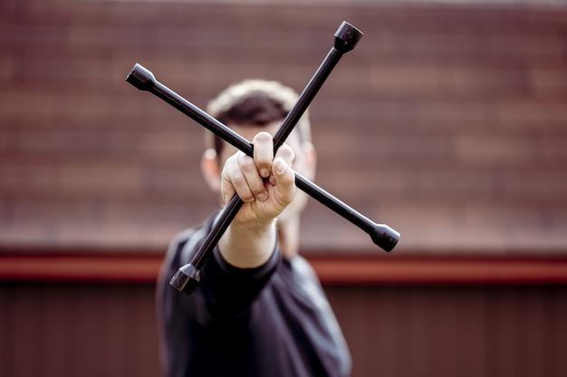 ホイールをインストールするための金属製のツールを保持している男のクローズアップショット
