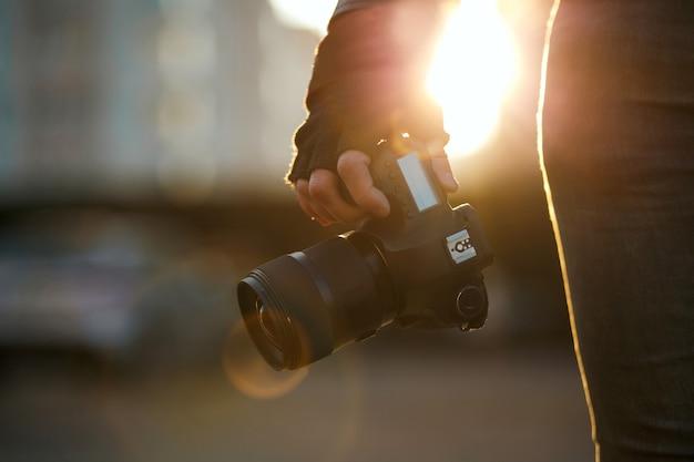 태양 빛에 대 한 디지털 카메라를 들고 장갑에 남자의 근접 촬영 쐈 어. 복사 공간