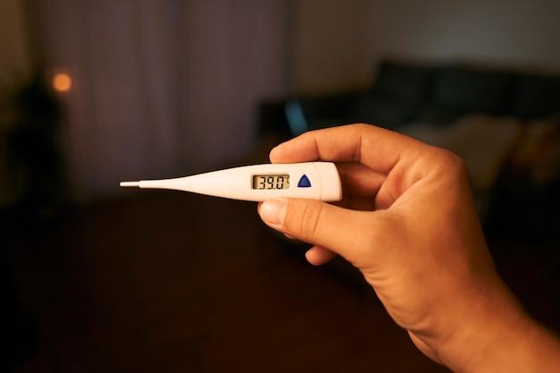 Снимок крупным планом человека, смотрящего на термометр. мужские руки, держа цифровой термометр.