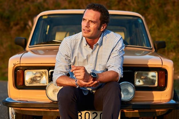 그의 오래 된 빈티지 자동차 앞에 앉아 남자의 근접 촬영 샷. 곱슬 모델 얼굴에 심각한 표정