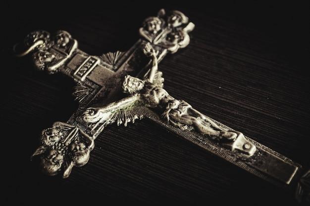 Металлический крест на черном деревянном столе крупным планом