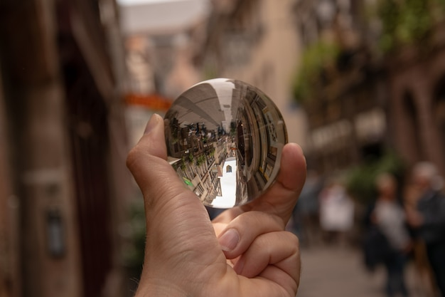 Снимок крупным планом человека, держащего хрустальный шар с отражением исторических зданий