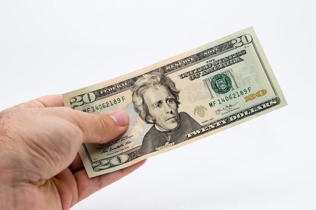 Снимок крупным планом человека, держащего долларовую купюру