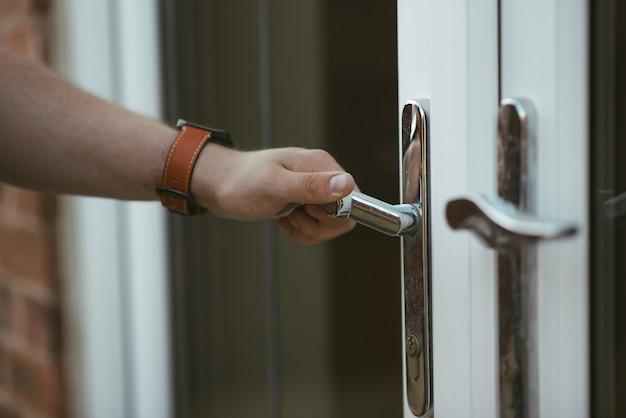문 손잡이를 잡고 문을 여는 사람의 근접 촬영 샷