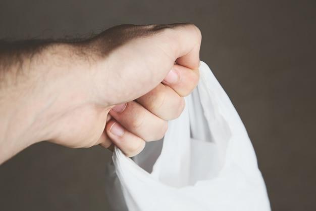 Снимок крупным планом человека, держащего продуктовую сумку