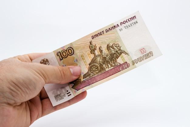 分離された白でいくつかの現金を保持している人のクローズアップショット