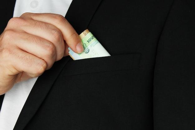彼のコートのポケットにいくつかの現金を入れている人のクローズアップショット
