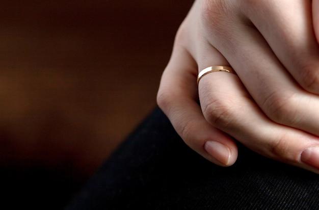 Макрофотография выстрел из руки человека с обручальным кольцом на коричневой поверхности