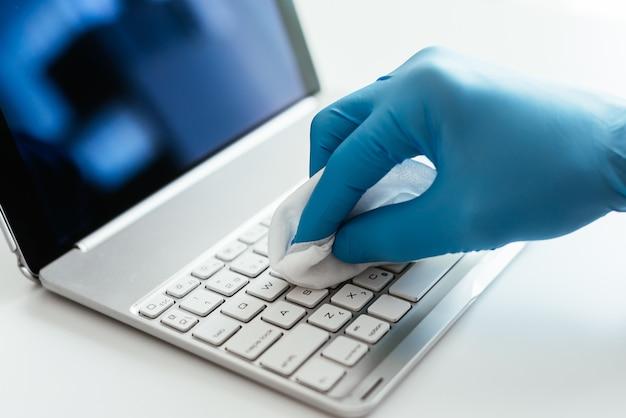 ノートパソコンのキーボードを消毒している人のクローズアップショット
