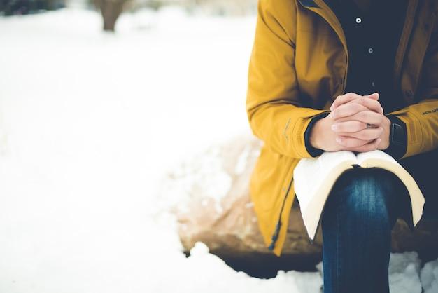 무릎에 성경과 함께 바위에 앉아기도하는 사람의 근접 촬영 샷
