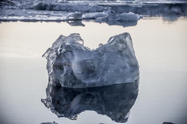 Крупным планом - кусок льда, плавающий в океане и отраженный в нем, в йокулсарлоне, исландия