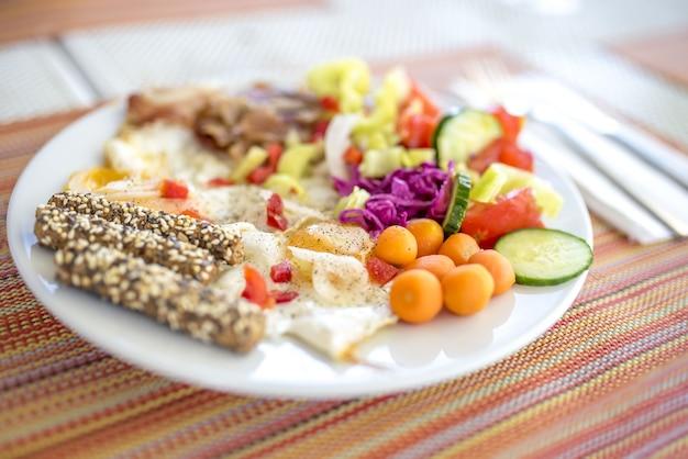 Снимок крупным планом тарелки с колбасой и овощами, готовыми к подаче