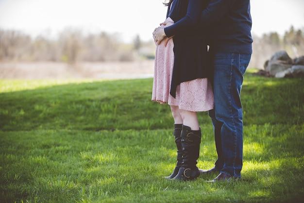 芝生のフィールドに立っている妊娠中のカップルのクローズアップショット