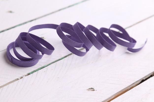 白い木の表面に分離された紫色のパーティーストリーマーのクローズアップショット
