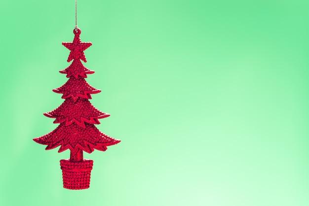밝은 녹색 배경에 빨간색 니트 크리스마스 트리 옷걸이의 근접 촬영 샷