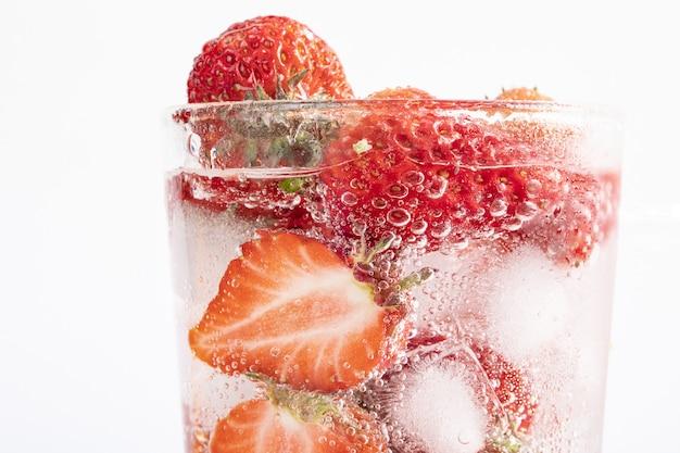 イチゴと角氷のスライスとさわやかな飲み物のクローズアップショット