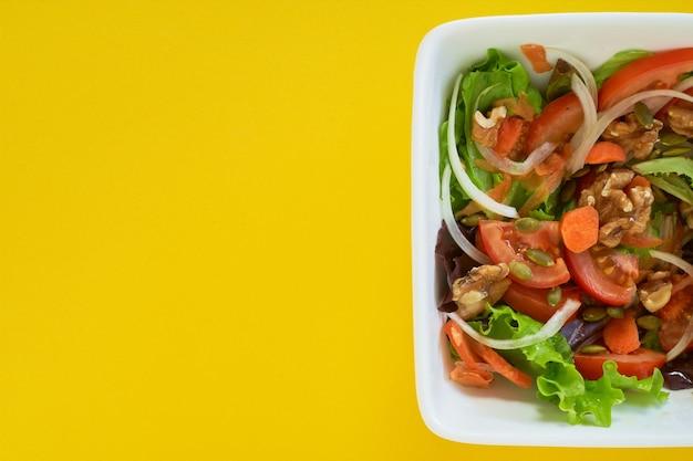 黄色の背景にサラダプレートのクローズアップショット。健康的なベジタリアン料理。テキスト用のスペース