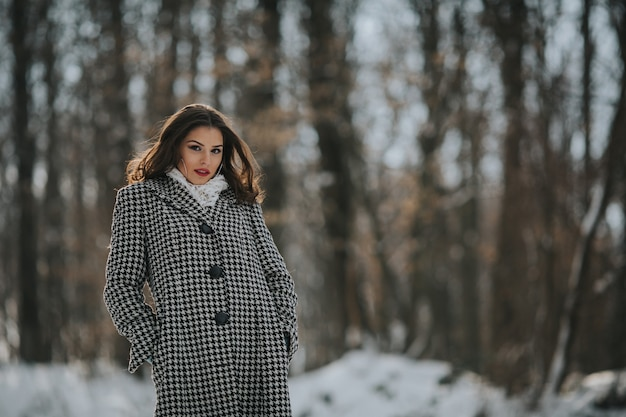 빨간 립스틱을 바르고 눈 덮인 공원에서 세련된 코트를 입은 섹시한 백인 여성의 클로즈업 샷