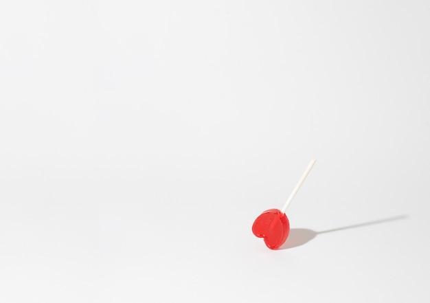 흰색 배경에 단일 하트 모양의 막대 사탕의 근접 촬영 샷