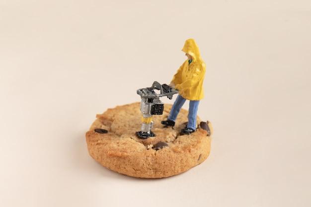 チョコレートクッキーに取り組んでいる小さな建設労働者のクローズアップショット
