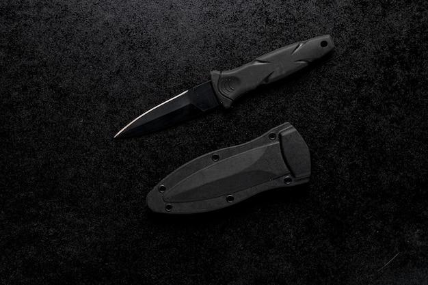 黒いテーブルに黒いハンドルが付いている小さな鋭いアーミーナイフのクローズアップショット