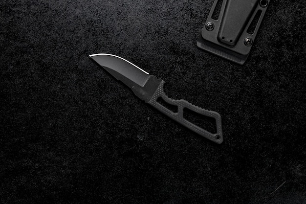 Крупным планом выстрелил небольшой острый нож с черной ручкой на черном фоне