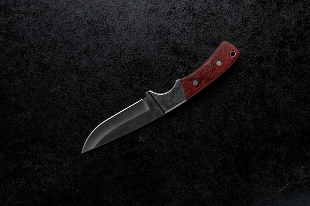 Крупным планом выстрелил небольшой острый нож с коричневой ручкой на черном фоне