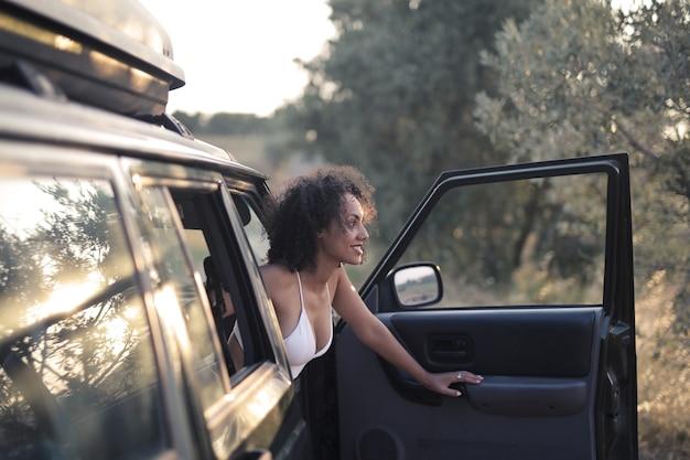 차에서 밖에 서 찾고 웃는 젊은 여자의 근접 촬영 샷
