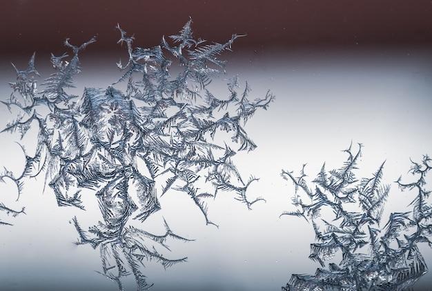 霜からガラスの上の雪の結晶のクローズアップショット