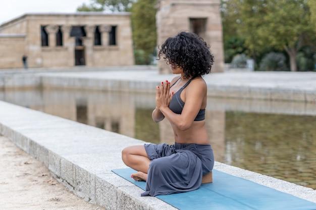 スペインの女性のクローズアップショットは、屋外でヨガを練習します