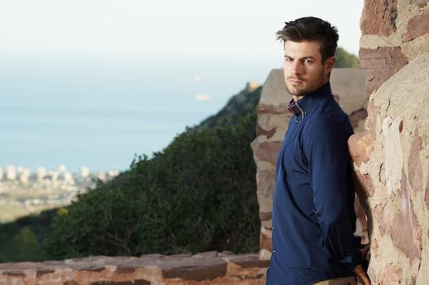 後ろに完璧な街の景色を望む彼の家の前でポーズをとっている成功した男性のクローズアップショット