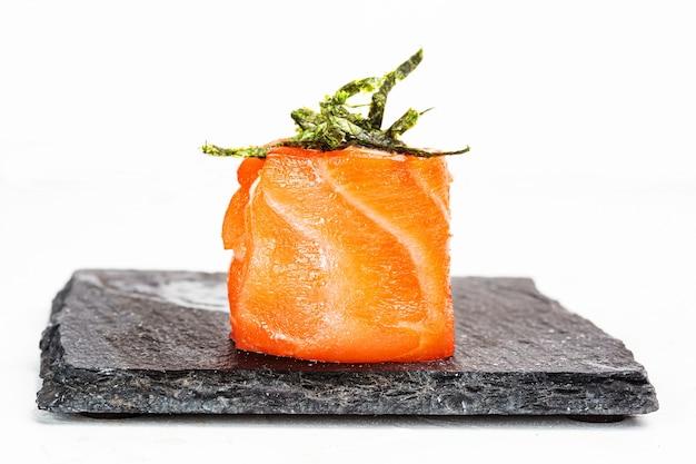 黒い石の皿に巻き寿司のクローズアップショット