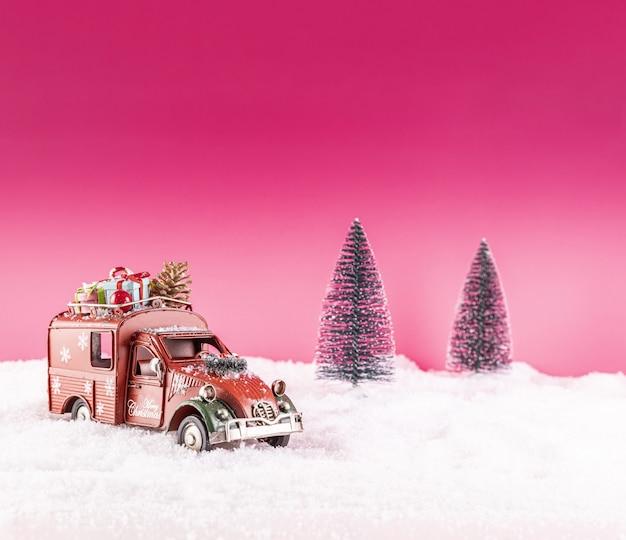雪の上のクリスマスの装飾のためのおもちゃの車のクローズアップショット
