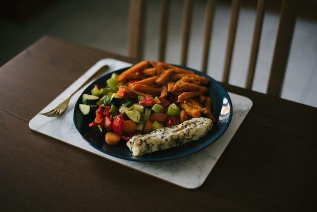 野菜サラダとジャガイモのクローズアップショットは、木製のテーブルに細かい千切りにカット