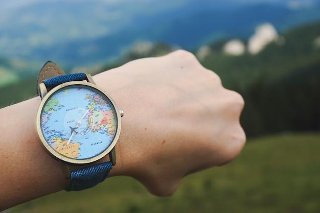 その上に世界地図と手に結ばれた時計のクローズアップショット