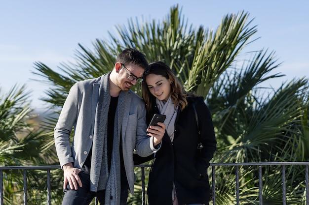 携帯電話を見ている女性と若い男性のクローズアップショット
