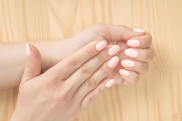 マニキュアを取得しているネイルサロンの女性のクローズアップショット。木製の背景。白ピンクの爪を持つ美しい手入れの行き届いた女性の手。完璧な、手入れの行き届いた女性の手ネイルケア。マニキュアビューティーサロン。