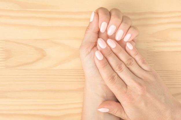 マニキュアを取得しているネイルサロンの女性のクローズアップショット。木製の背景。白ピンクの爪を持つ美しい手入れの行き届いた女性の手