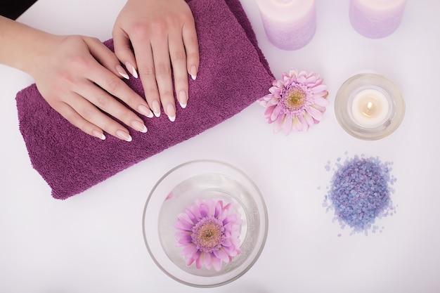 アセトンとコットンウールの美容師によるマニキュアを受けるネイルサロンでの女性のクローズアップショット。