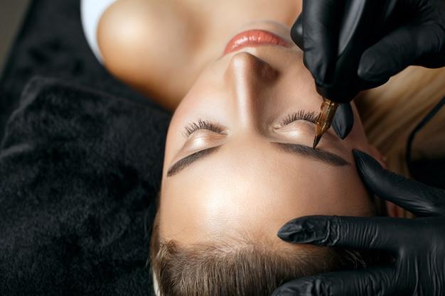 若い女性に恒久的な額の化粧を適用する黒い手袋の女性のクローズアップショット。テキスト用のスペース