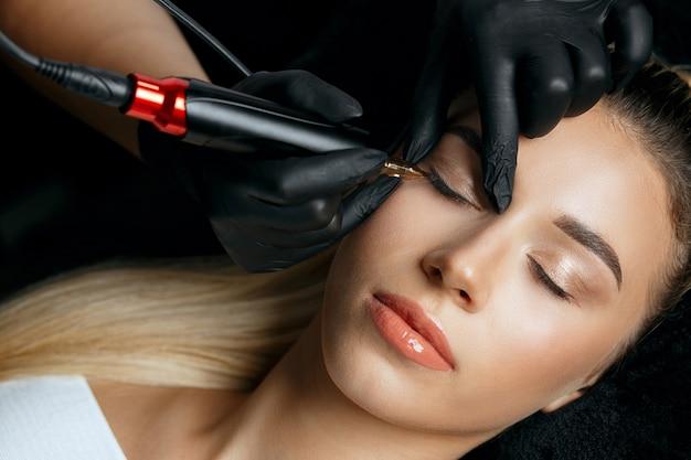 美容院で若い女性のクライアントに恒久的なまぶたの化粧をしている黒い手袋の女性のクローズアップショット。上面図