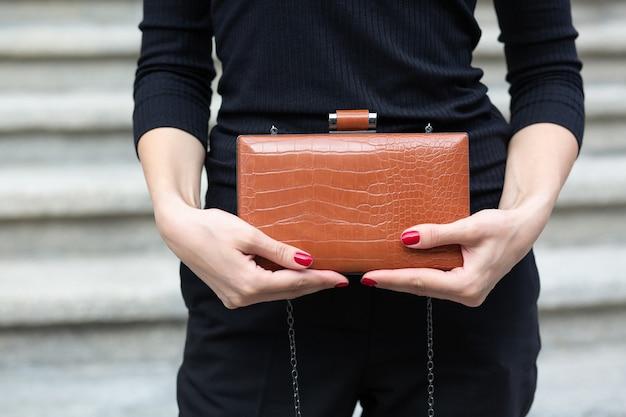 小さな革の茶色の財布を持っている女性の手のクローズアップショット。空きスペース