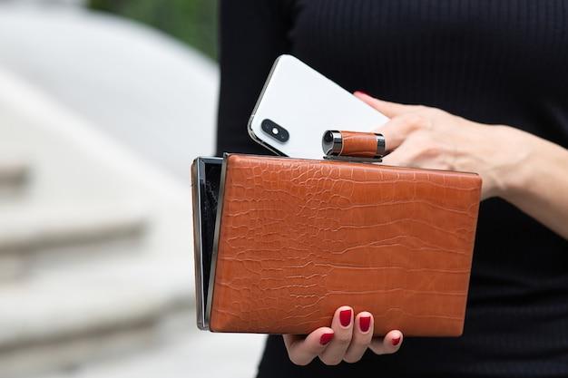 女性の手のクローズアップショットは、小さな財布から携帯電話を取り出します。空きスペース